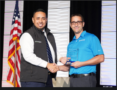 Daniel Galindo, SVP, CRA and Strategy Director, Woodforest National Bank, accepting the Wolters Kluwer's 2019 Community Impact Award from Nick Hammerstad, VP of Sponsor Acquisition for Banzai Inc., the award sponsor